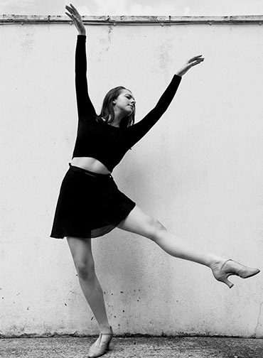 Paris Hoxton in a dance pose with her arms stretched above her head and one leg raised off the ground.