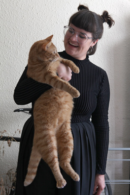 Celia smiles and holds a large cat.