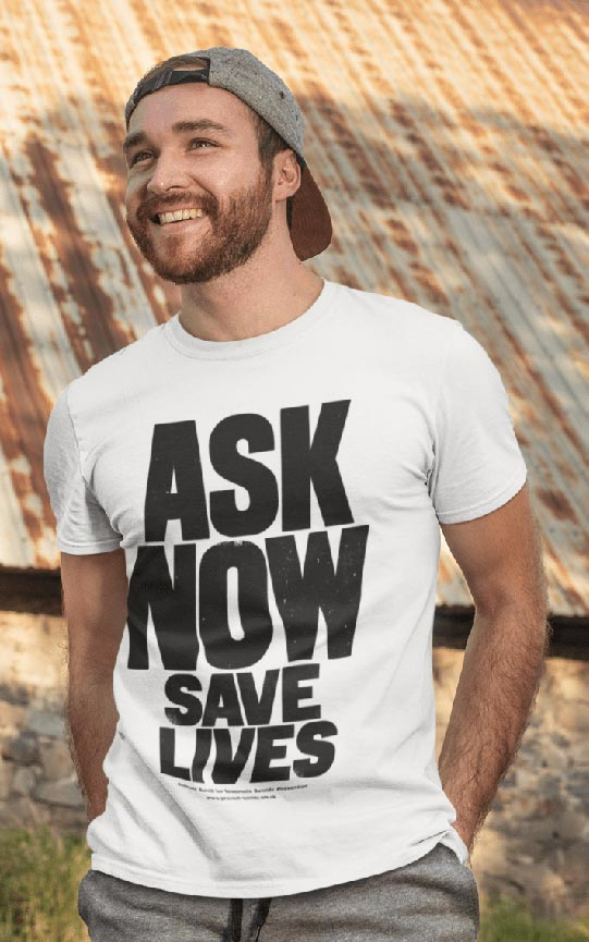 A man wears a white t-shirt with the Ask Now Save Lives design on the front.