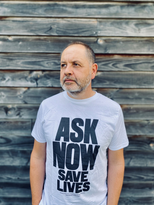Anthony Burrill wears his black and white Ask Now Save Lives Later T-Shirt.