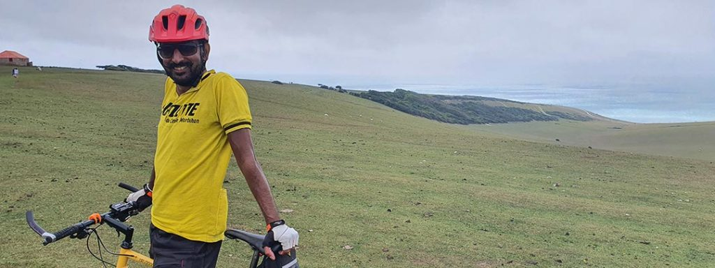 Natty astride his bike in a yellow vest with the coastline behind him.