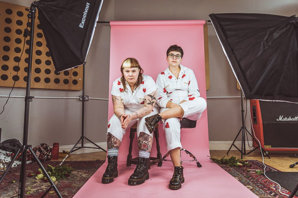 Hannah (left) and Clara (right) sat in a studio with a pink backdrop.
