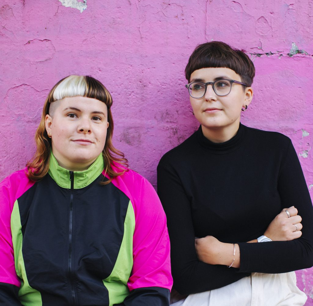 Hannah (left) and Clara (right) stand against a pink wall.