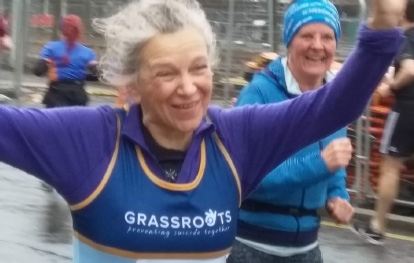A grey-haired woman running in a Grassroots vest. Her arms are raised.