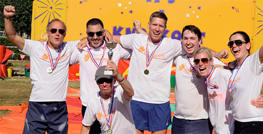 7 people celebrate wearing grassroots T-shirts and sporting new medals.
