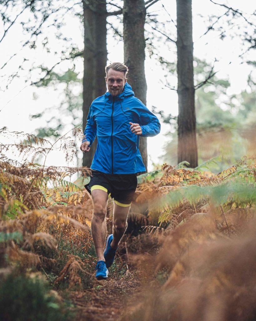 Rich Williamson running through a forest in running gear.