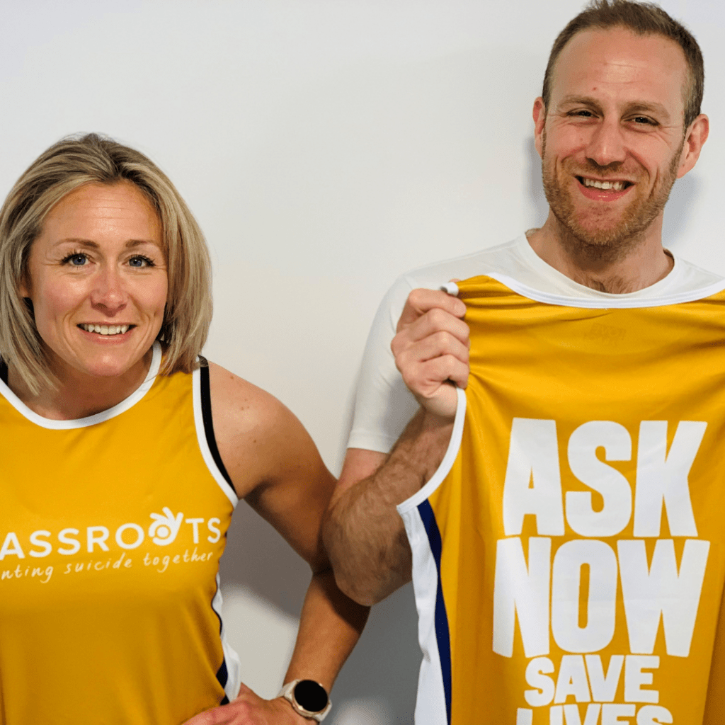 A woman and man smiling, both holding Grassroots Runners vests.