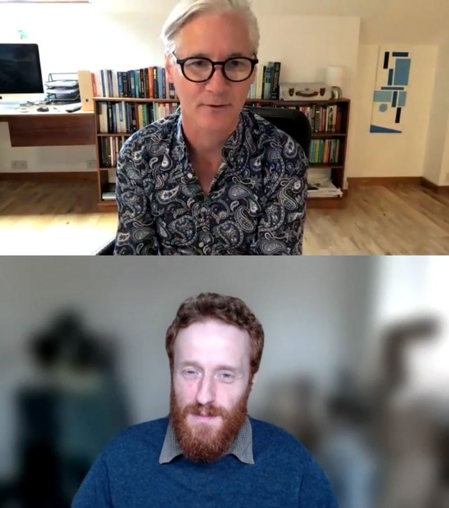 Rory (a fresh-faced looking pale man with smart white hair and round black glasses) sits in a desk chair. Some way behind him are a desk, computer, and a long bookshelf. Alex from Grassroots (A man with a smart red beard and short hair) listens as Rory talks.