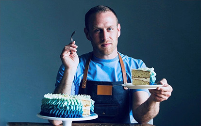 A baker sits behind a large frosted cake. He holds a fork and a slice of cake on a plate.