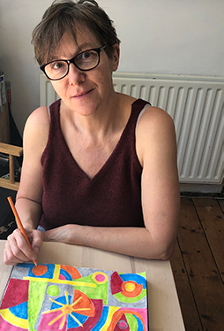 Agnes (a woman with shortish hair and glasses) sits at a table with an orange pencil completing an abstract, sunny painting.