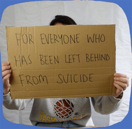 """A woman holds up a cardboard sign with the words """"For everyne who has been left behind from suicide."""""""