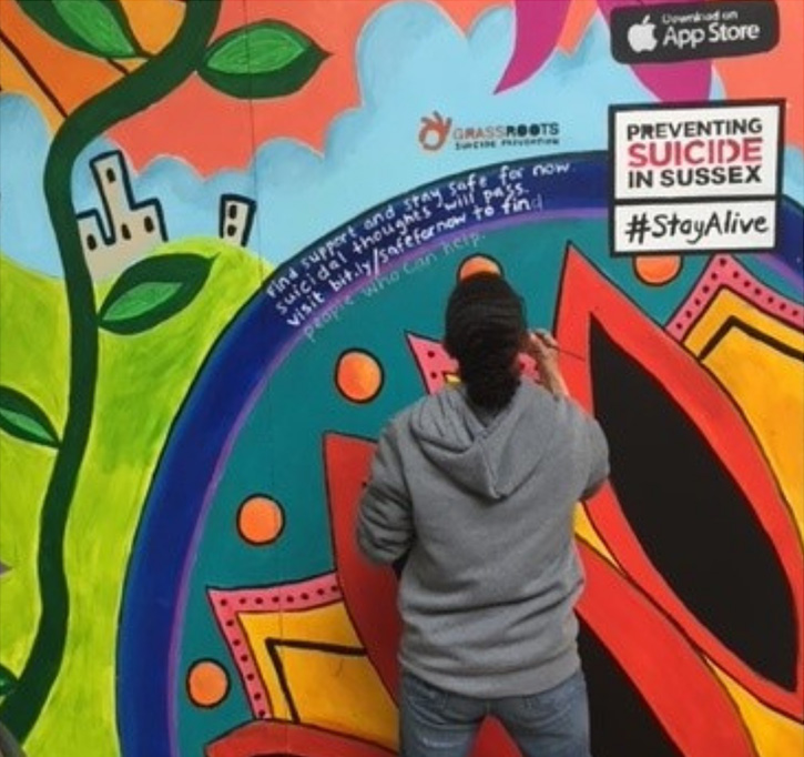 A woman with her back to us and wearing a hoodie does some detail work on a brightly-painted outside wall.